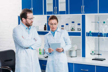 portrait of scientific researchers in lab coats with digital tablet in laboratory