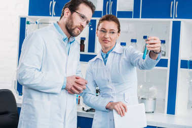 portrait of scientists in eyeglasses looking at tube with reagent in laboratory