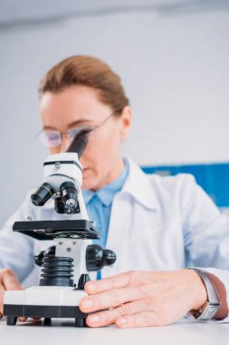 selective focus of female scientist in lab coat and eyeglasses looking through microscope on reagent in lab