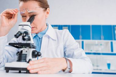 Female scientist in lab coat and eyeglasses looking through microscope on reagent in lab stock vector