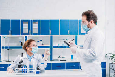 scientists in white coats and goggles working with reagents and microscope in laboratory