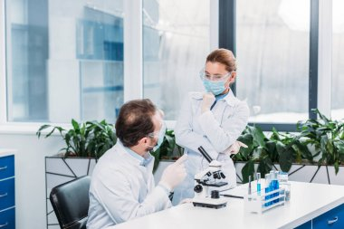 scientists having discussion at workplace in laboratory