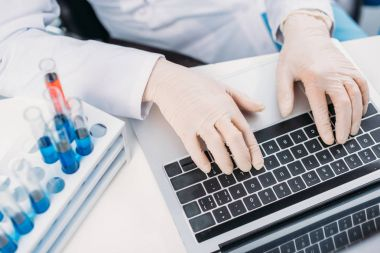 partial view of scientist in lab coat and medical gloves typing on laptop at workplace with reagents