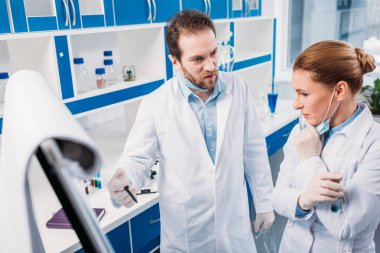 scientist in white coats near board for notes having discussion during work in lab