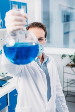 selective focus of scientist with flask in hand in lab