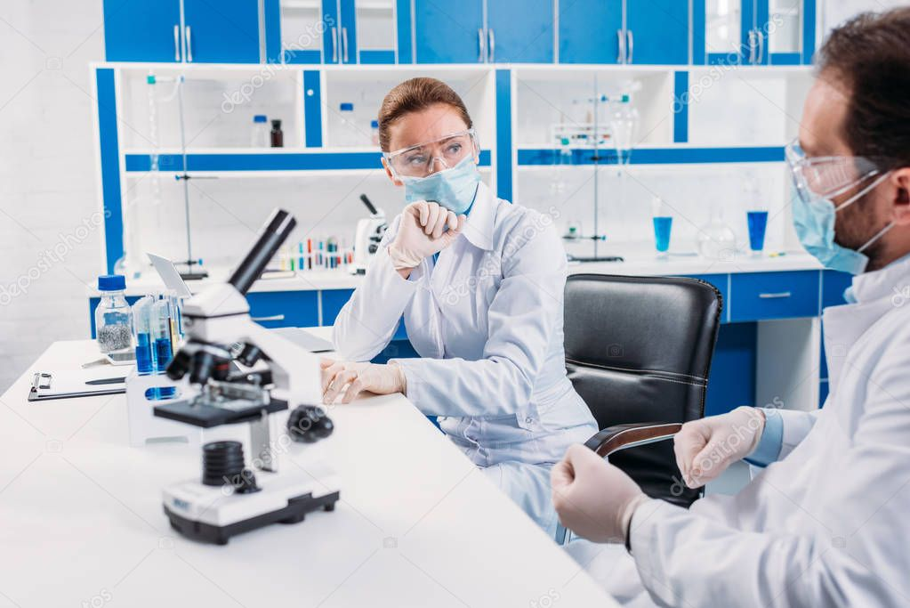 scientific researchers in medical masks and goggles having discussion at workplace with microscope in lab