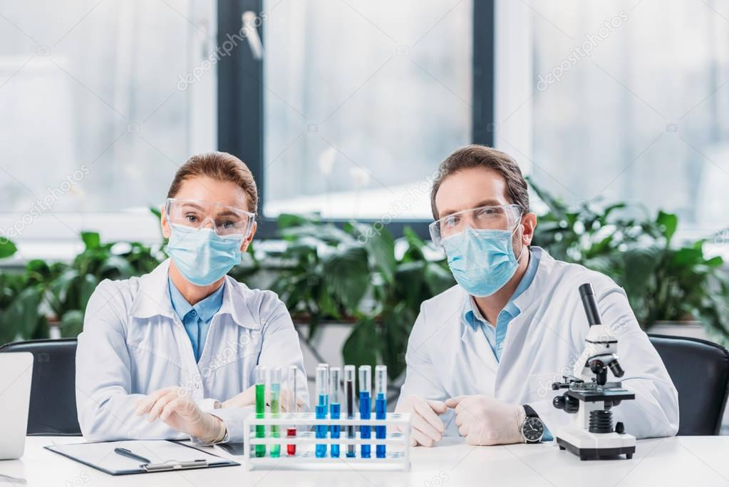 Scientific researchers in goggles and medical masks sitting at workplace with reagents in tubes and microscope in lab