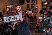 Happy bike opravy stanice pracovník na otevřené dávaného v garáži