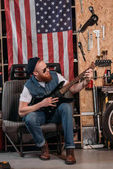 Fotografie handsome bearded man playing electric guitar at garage with usa flag hanging on wall
