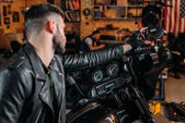 Fotografie stylish young man in leather on bike at garage