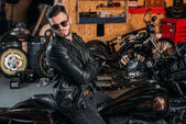 Fotografie handsome young man in sunglasses and leather jacket on bike at garage
