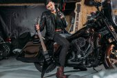 Fotografie stylish young man in leather jacket sitting on bike with electric guitar at garage