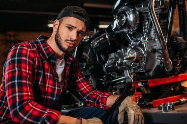 handsome bike repair station worker with wrench sitting in front of motorcycle and looking at camera
