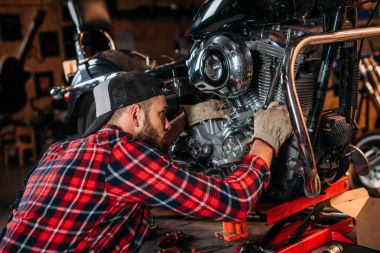 close-up shot of bike repair station worker fixing motorcycle