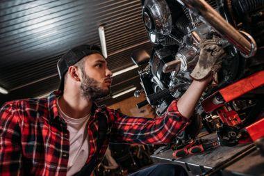 handsome bike repair station worker fixing motorcycle