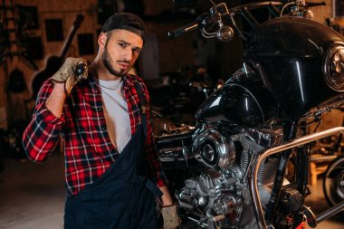 handsome bike repair station worker with wrench in front of motorcycle