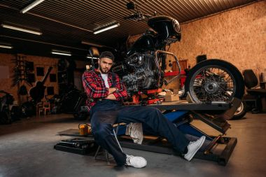 bike repair station worker sitting in front of motorcycle at garage