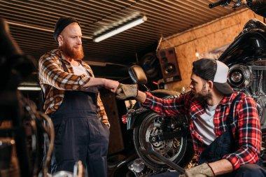 Handsome mechanics making bro fist at motorcycle repair garage stock vector