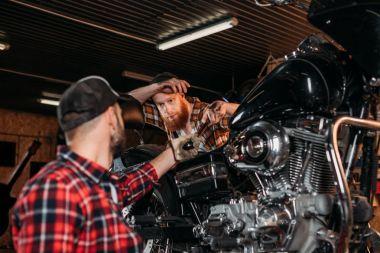 handsome mechanics repairing motorcycle together at custom garage