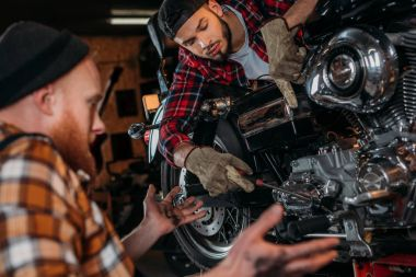 concentrated mechanics repairing motorcycle together at garage