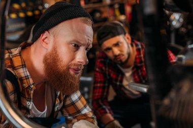Handsome mechanics looking at motorcycle to repair at garage stock vector