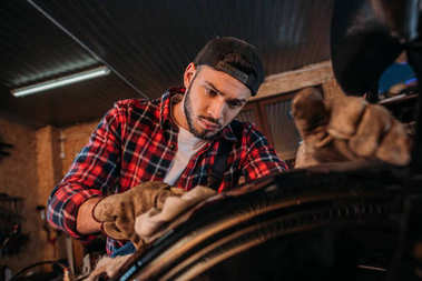 close-up shot of bike repair station worker cleaning wheel at garage