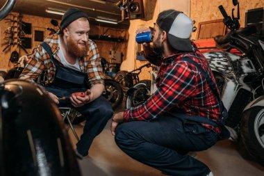 Young mechanics having break in work at garage stock vector
