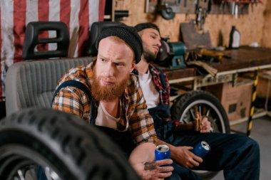 handsome mechanics having break in work at garage