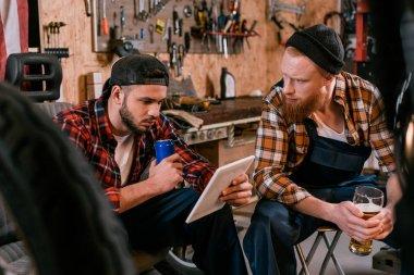handsome mechanics with tablet drinking beer at garage