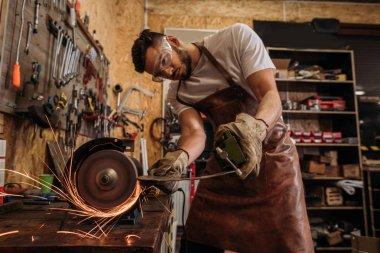 handsome repair workshop worker using grinding machine at garage