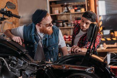 repair worker talking to customer near motorcycle at garage