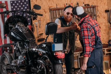 repair worker greeting customer at custom garage