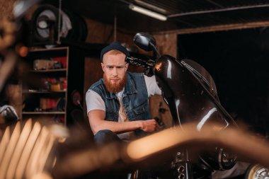 portrait of handsome young man on bike at garage