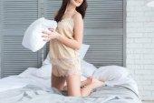 částečné zobrazení ženy v pyžamu s polštářem v ruce na posteli