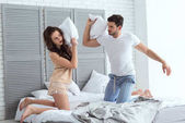 Fotografie young couple in pajamas having pillow fight on bed at home
