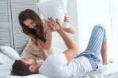 young couple in pajamas having pillow fight on bed at home
