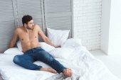 Fotografie mladý atraktivní muž v džínách, ležící na posteli