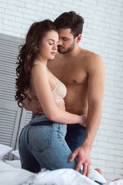 young seductive couple in jeans hugging on bed at home