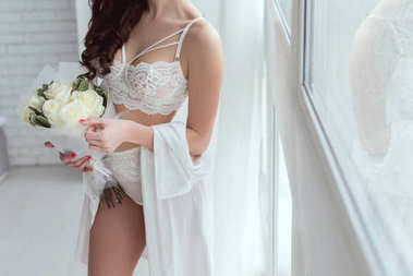 cropped shot of woman in underwear with bouquet of roses standing at window