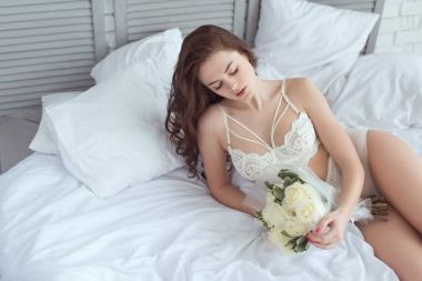 sexy woman in white underwear with bouquet of roses resting on bed