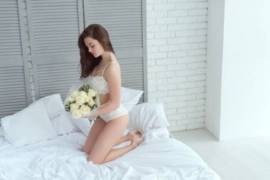 young woman in white underwear with bouquet of roses on bed at home