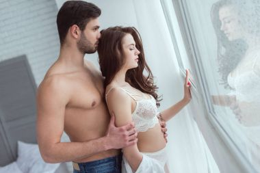 man hugging sexy woman in lingerie while standing at window
