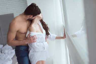 side view of young sexy couple standing at window at home