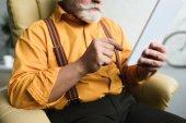 Fotografie cropped shot of bearded senior man using digital tablet at home