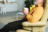 Fotografie cropped shot of bearded senior man holding cup and sitting on armchair at home