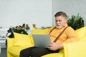 lächelnder bärtiger älterer Mann mit Laptop, während er zu Hause auf der Couch sitzt