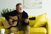 Fotografie pensive bearded senior man playing guitar and looking away at home