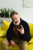 Fotografie excited bearded senior man showing rock gesture and screaming at camera