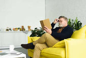 Fotografie bearded senior man in eyeglasses sitting on yellow couch and reading book