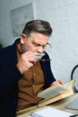 Fotografie bearded senior man adjusting eyeglasses and reading book at home